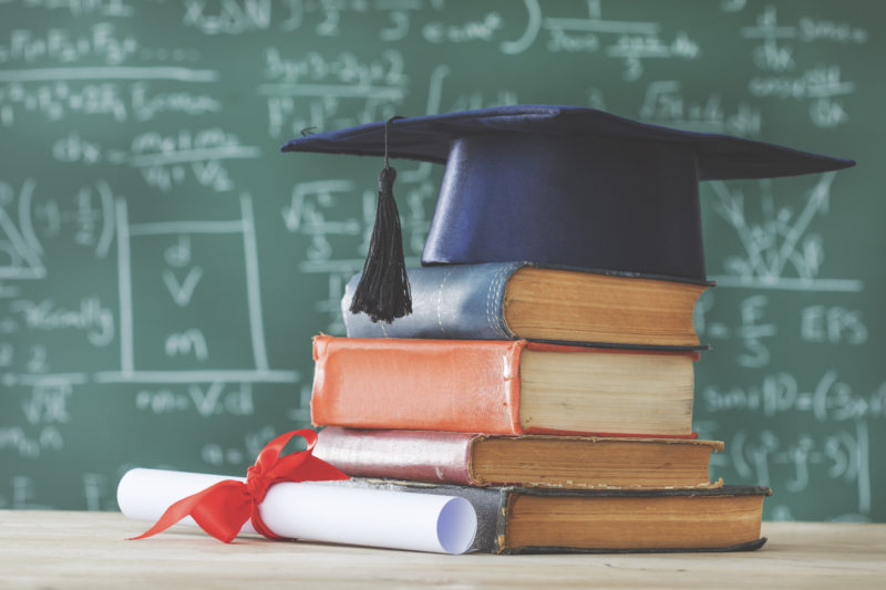 Stack of books with diploma and graduation cap