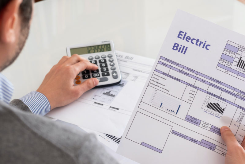 Man holding electric bill and using calculator