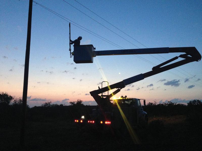 linemen working on poles at night