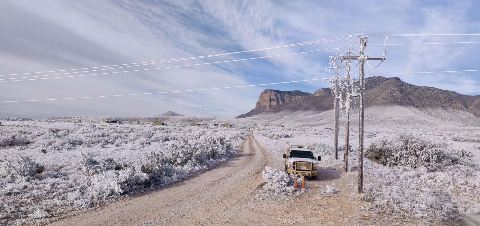 bucket truck near power line with mountains in the distance