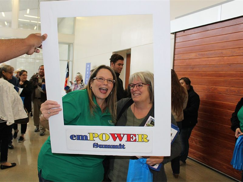 two women posing with empower summit sign