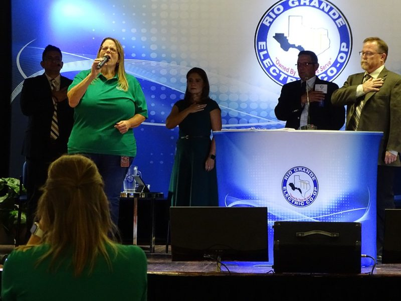 Woman singing national anthem at annual meeting