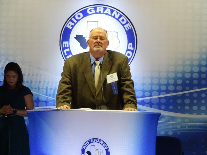 man speaking at podium at annual meeting