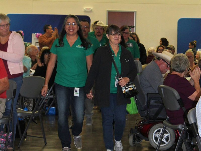 RGEC staff walking through the room to applause from members
