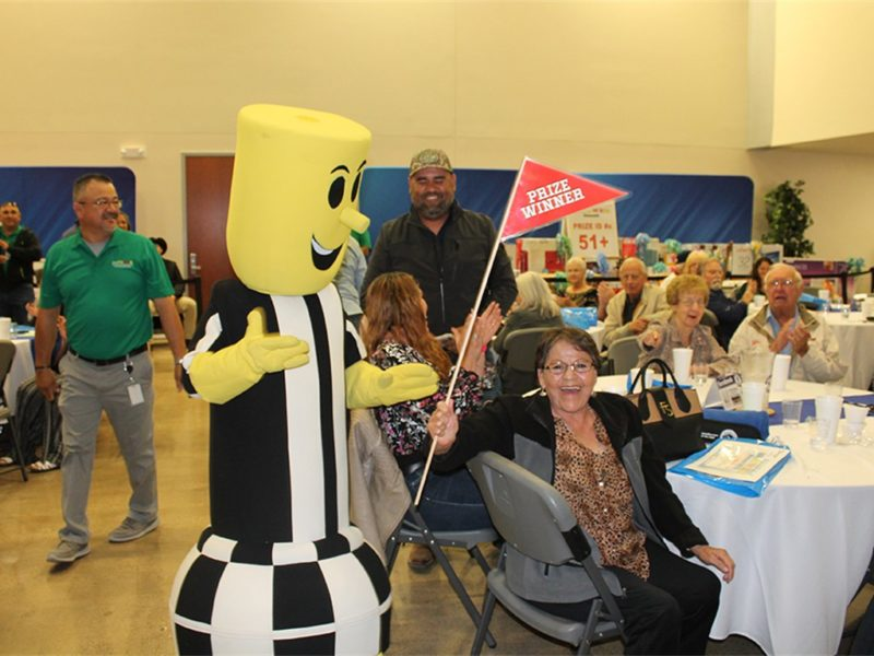 electricity mascot waving prize winner flag next to a smiling woman
