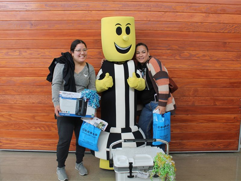 girls posing with electricity mascot