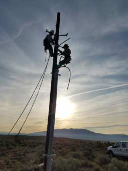 two linemen at top of power pole during sunset