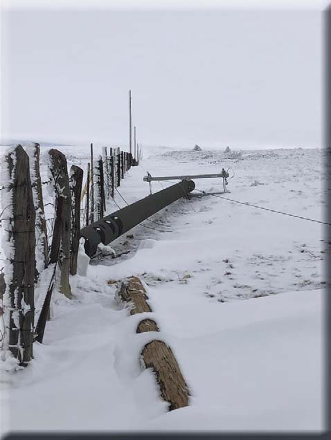 broken power poles on the ground in the snow