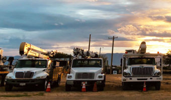 bucket trucks in a row with sunset behind them